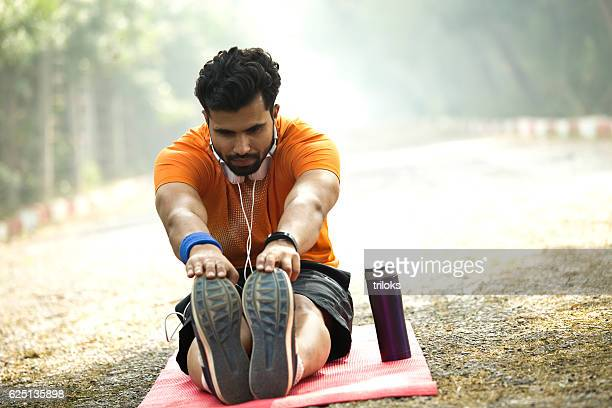 Man stretching on yoga mat at park