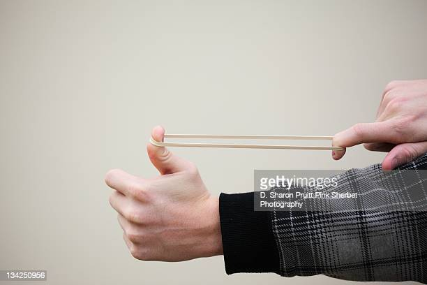 Man stretching rubber band