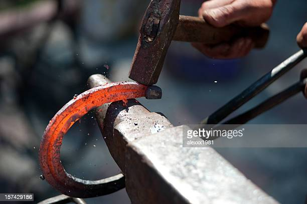 A man striking a red hot horseshoe on the anvil