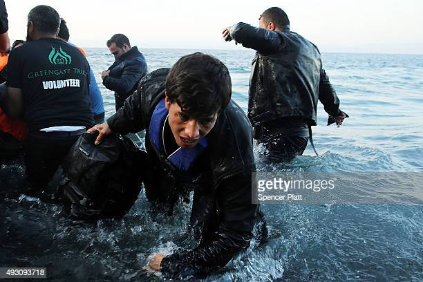 A man struggles in the water as a raft carrying migrants arrives from Turkey onto the island of Lesbos on October 17 2015 in Sikaminias Greece Dozens...