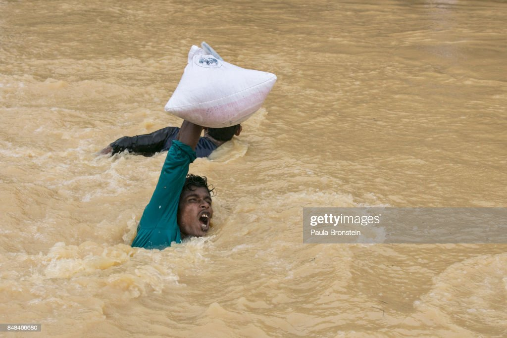 A man struggles to carry supplies across a stream as the monsoon rains continue to make life miserable for the displaced Rohingya September 17, 2017 in Kutupalong, Cox's Bazar, Bangladesh. Nearly 400,000 Rohingya refugees have fled into Bangladesh since late August during the outbreak of violence in the Rakhine state. Recent satellite images released by Amnesty International provided evidence that security forces were trying to push the minority Muslim group out of the country. Myanmar's de facto leader Aung San Suu Kyi cancelled her trip to the United Nations General Assembly in New York, which begins next week, while criticism of her handling of the Rohingya crisis grows and her government has been accused of ethnic cleansing. According to reports, the Rohingya crisis has left at least 1,000 people dead, including children and infants. Dozens of Rohingya Muslims drowned when their Ill-equipped, overloaded boat capsized in rough waters.