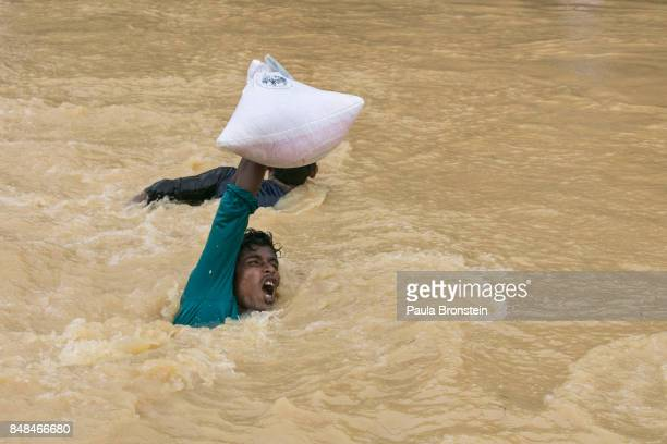 A man struggles to carry supplies across a stream as the monsoon rains continue to make life miserable for the displaced Rohingya September 17 2017...