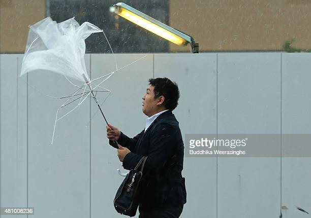 A man struggles to hold an umbrella against strong wind and rain delivered by typhoon Nangka on July 17 2015 in Himeji Japan As Typhoon Nangka made...