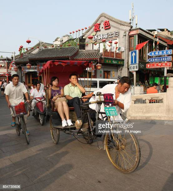 A man struggles with a rickshaw near Hou Hai lake in Old Beijing China