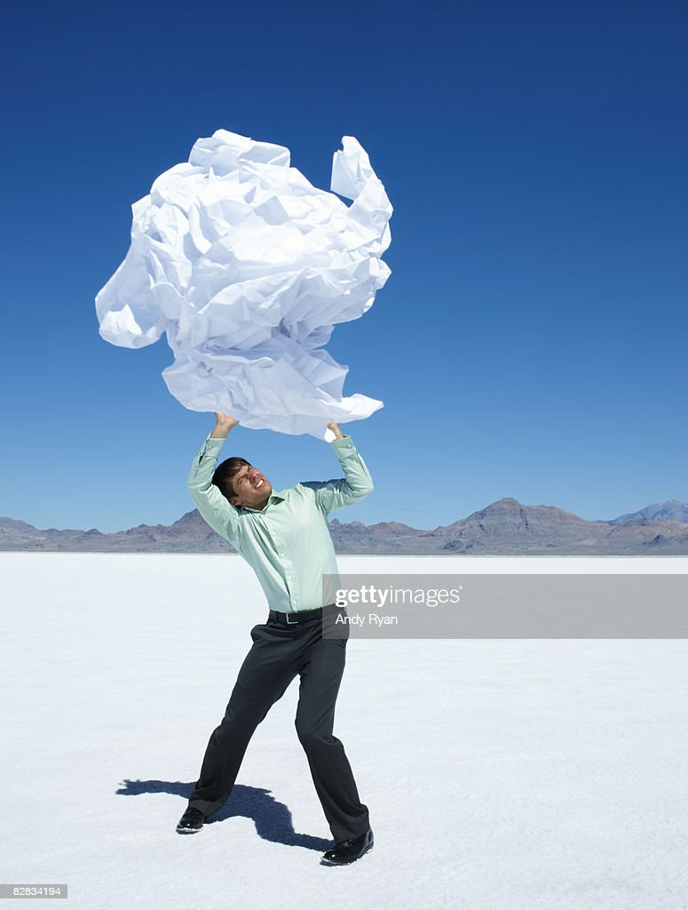 Man Struggling to Hold Up Giant Wad of Paper : Stock Photo