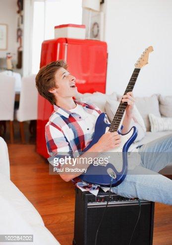 Man strumming guitar and singing : Stockfoto