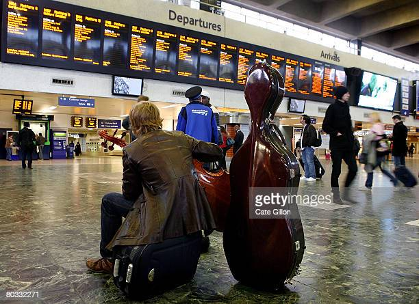 A man strums on his cello while waiting for details of his train journey to appear on the Departure screen at Euston station on March 21 2008 in...