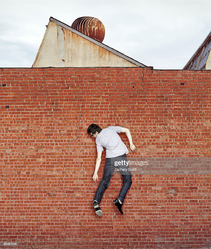 man stuck weightlessly on red brick wall