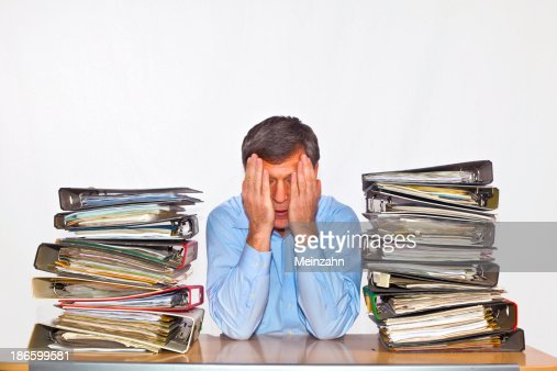 man studies folder with files at his desk : Stock Photo