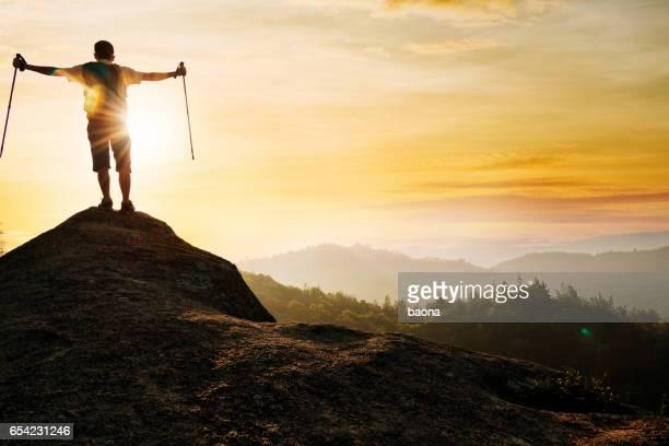 Man success standing at mountain peak