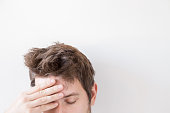 Man suffering from daily headache and touching his forehead with hand. Problem concept. Empty place for a text or object on the gray background.
