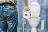 Man suffers from diarrhea holds toilet paper roll in front of toilet bowl.