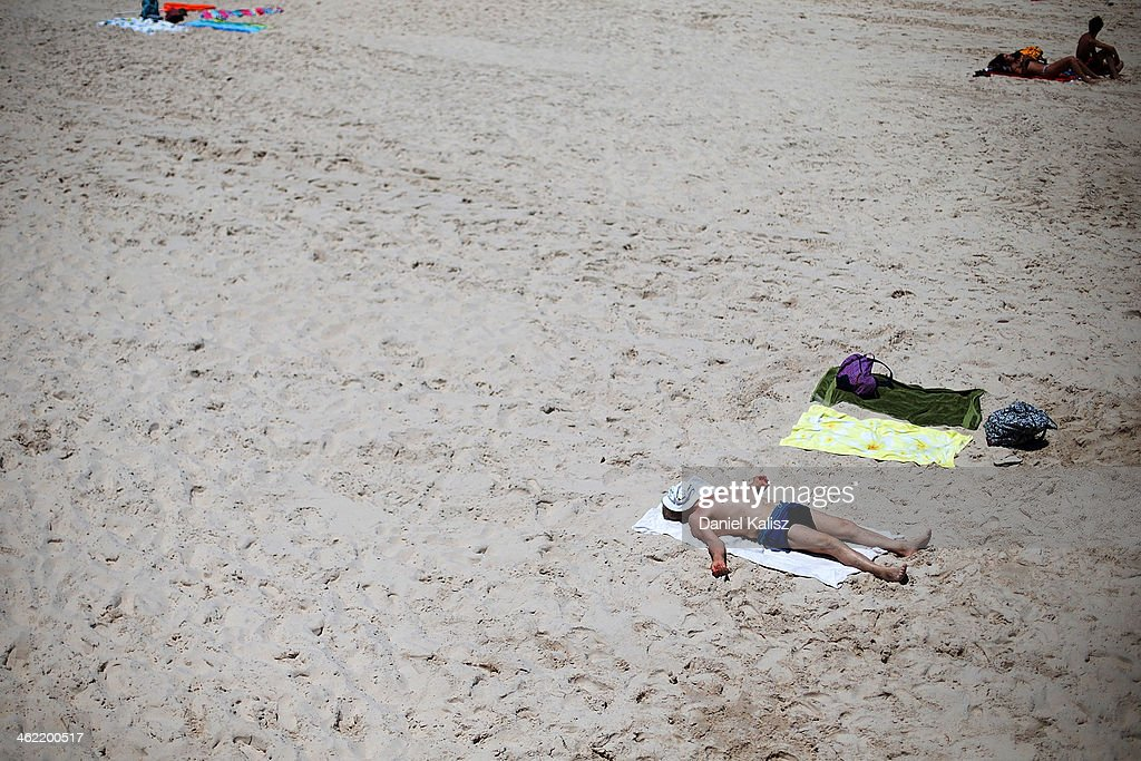 A man sunabathes in the midday sun during a heat wave at Glenelg beach on January 13, 2014 in Adelaide, Australia. Temperatures are expected to be over 40 degrees celsius all week with health authorities warning the young and elderly to remain indoors.