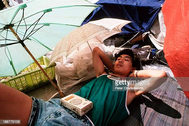 A man sunbathes and listens to a transistor radio as Tiananmen Square takes on a beachlike atmosphere Prodemocracy demonstrators and protestors...