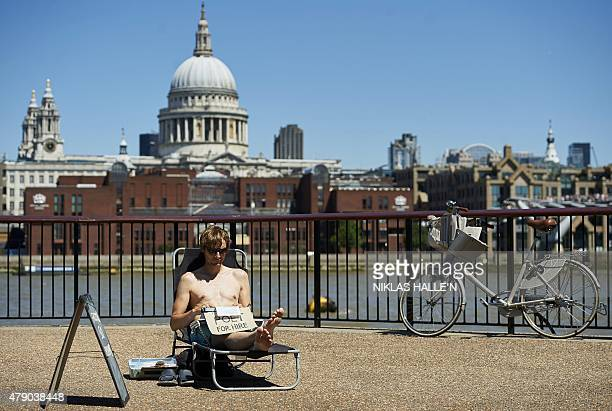 A man sunbathes beside the River Thames in central London on June 30 2015 Temperatures soared above 40 degrees in Spain and Portugal on Monday...