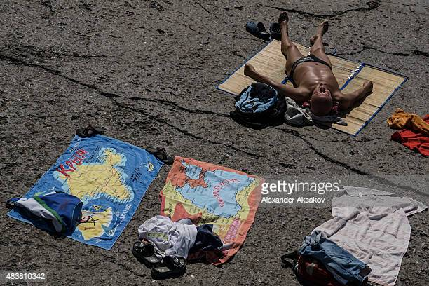 A man sunbathes next to a towel with a map of the Crimea on August 11 2015 in Yalta Crimea Russian President Vladimir Putin signed a bill in March...