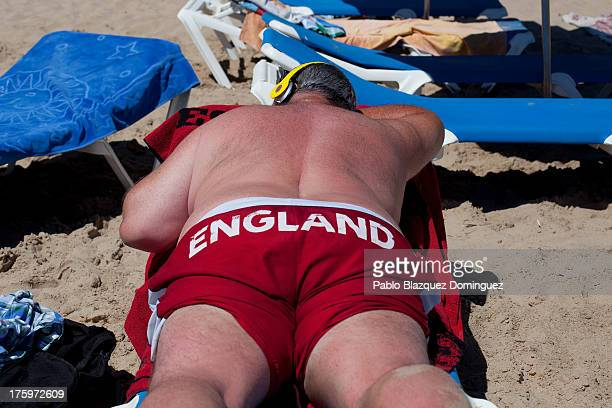 A man sunbathes on Levante Beach on August 10 2013 in Benidorm Spain Benidorm is one of Europe's top package holiday destinations and one of Spain's...