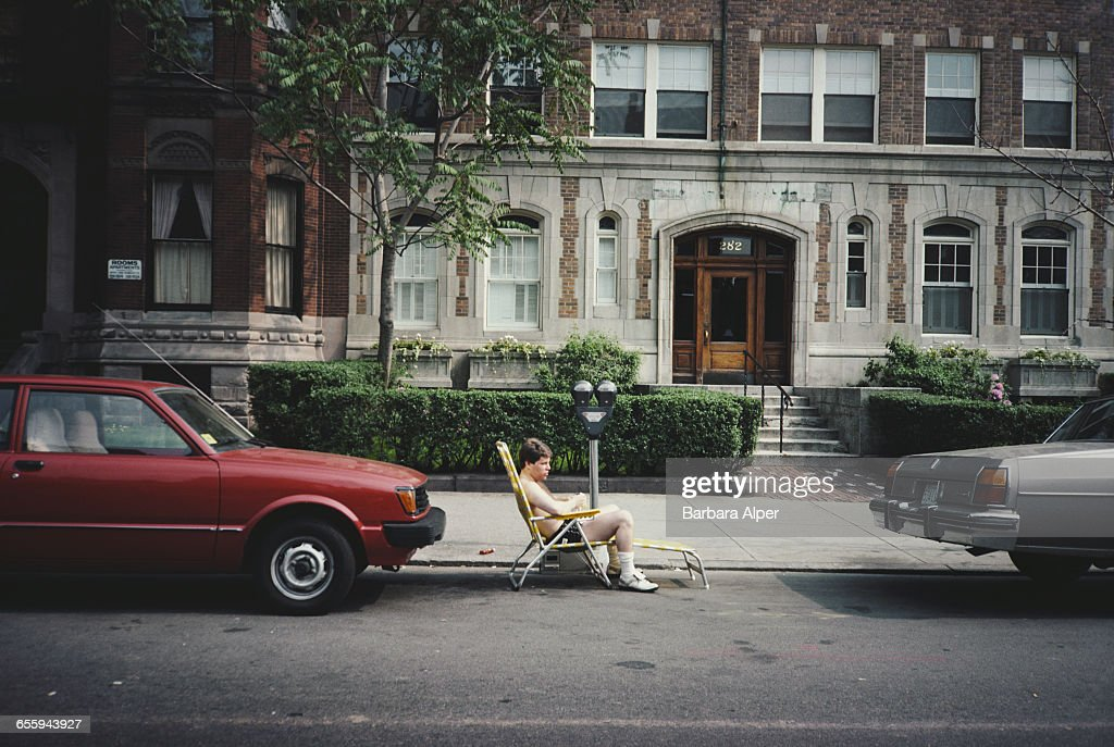 A man sunbathing by the curb outside 282 Newbury Street, Boston, Massachusetts, June 1986.