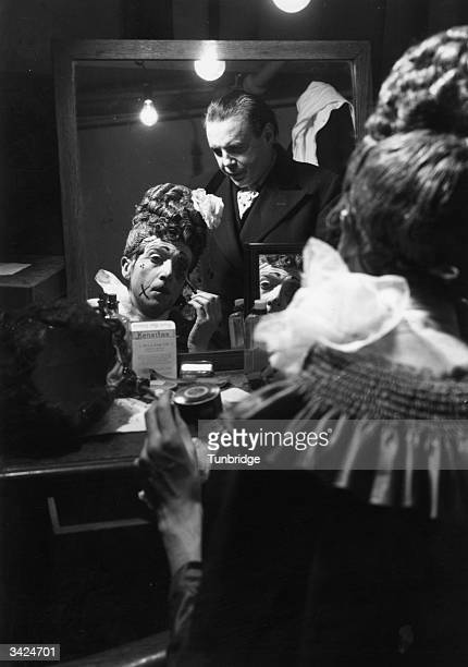 A man supervises an actor's application of makeup in a theatre dressing room