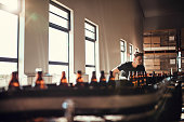 Young man supervising the production of craft beer at brewery. Man working at alcohol manufacturing factory.