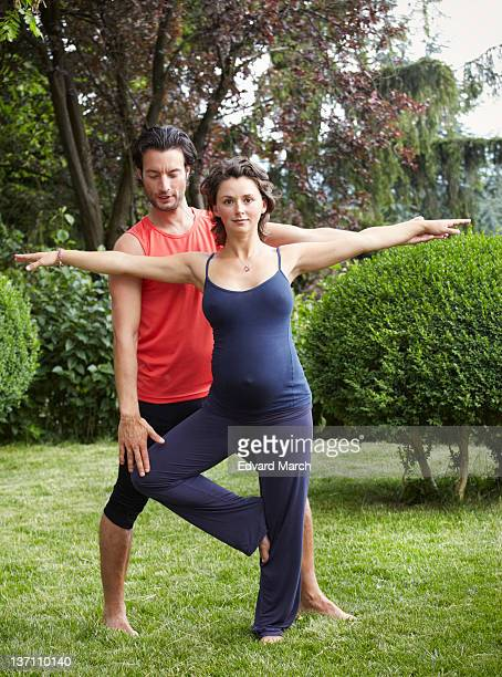 Man supporting pregnant woman doing gymnastics in garden