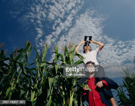Man supporting woman using binoculars in corn field, low angle view : Stockfoto
