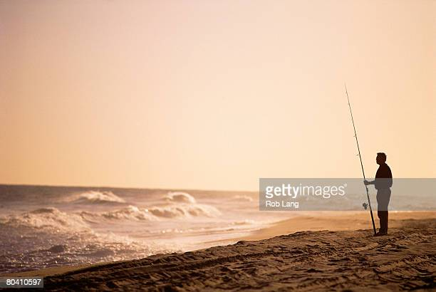 Man surf fishing on a beach