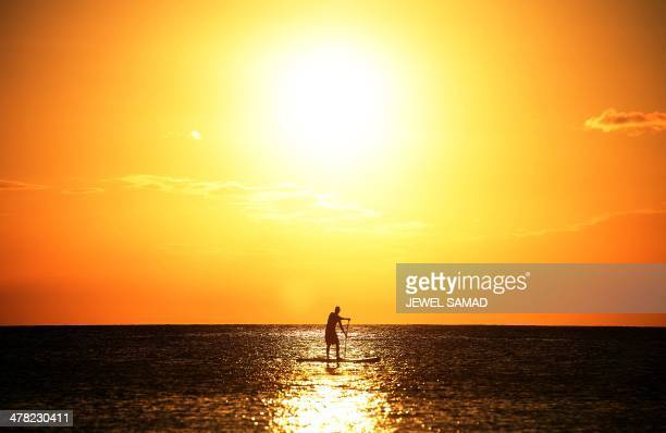 A man surf paddles near a beach as sun sets in Bridgetown on March 12 2014 AFP PHOTO/Jewel Samad