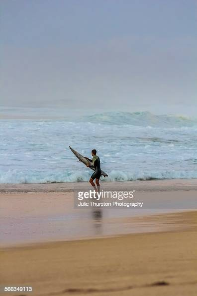 Man surfer heads in on beach with surfboard after riding massive teal foaming waves under a vibrant peaceful pink orange purple sky and reflections...