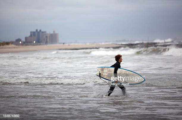 A man surfs at Rockaway Beach as Hurricane Sandy approaches on October 28 2012 in the Rockaway Beach neighborhood of the Queens borough of New York...