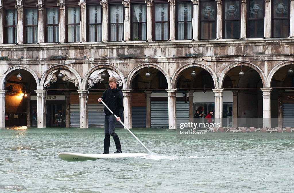 A man surfs in Saint Mark's Square during the exceptional High Water on November 11, 2012 in Venice, Italy. More than 70% of Venice has been been left flooded, after the historic town was hit by exceptionally and unexpected high tide. The sea level rose very quickly to 150 due as well to strong southerly wind and heavy rain.