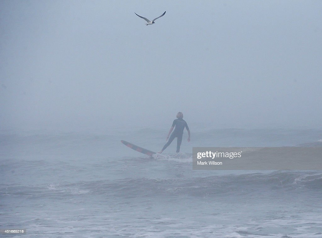 A man surfs in the fog as strong winds and heavy surf from Hurricane Arthur begin to roll in, July 3, 2014 in Nags Head, North Carolina. Hurricane warning has been issued for North Carolina's Outer Banks due to approaching Hurricane Arthur.