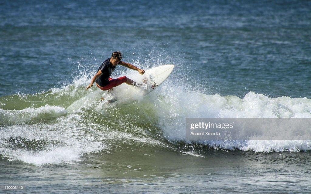 Man surfs waves on sunlit sea : Stock Photo