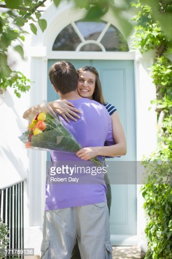 Man surprising girlfriend with bouquet of roses : Stock Photo