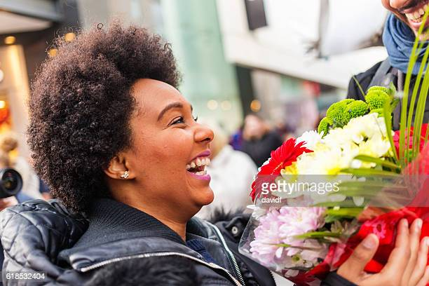 Man Surprising Woman With Flower Bouquet Gift While Shopping