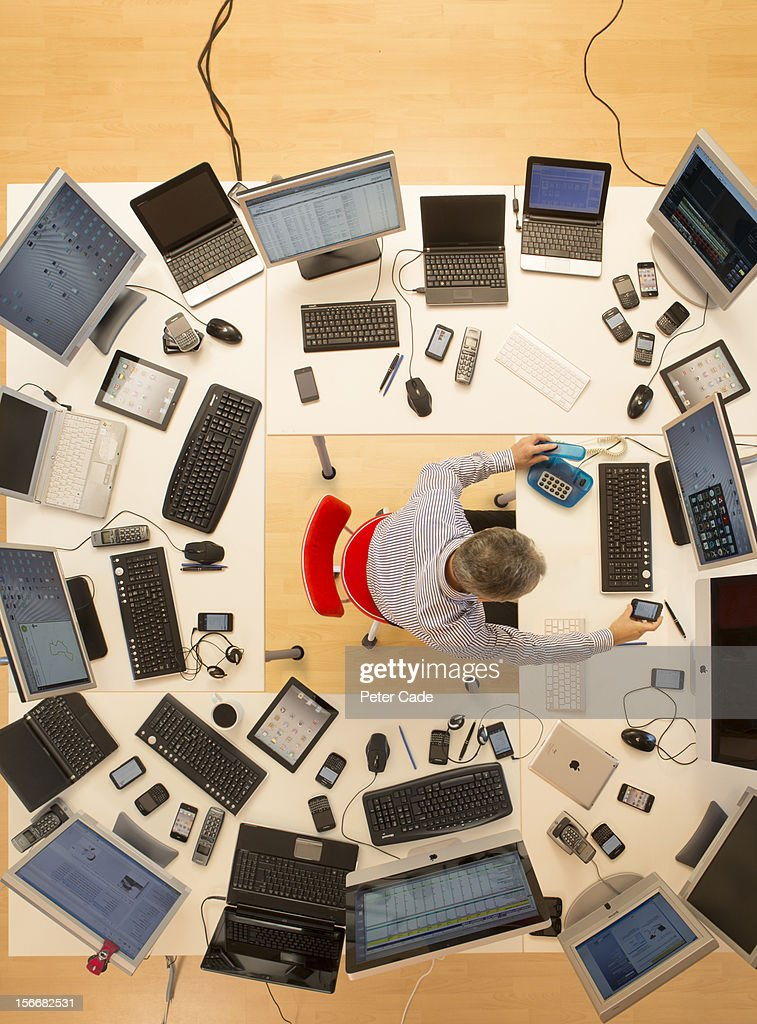 Man surrounded by desks and computers : Stock Photo