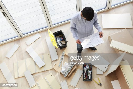 Man surrounded by unassembled furniture