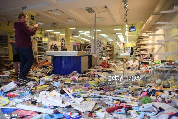 A man surveys the scene inside a looted Budnikowsky pharmacy following a second night of violent protest on July 8 2017 in Hamburg Germany Leaders of...