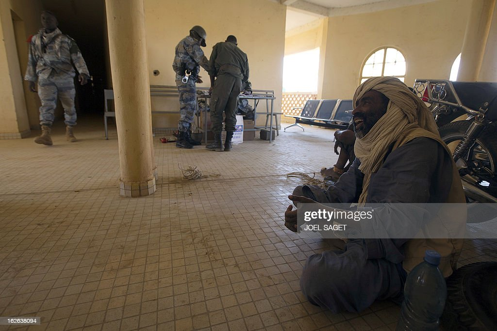 A man (R), suspected to be a member of Islamist armed group the Movement for Oneness and Jihad in West Africa (MUJAO) sits on the ground as he waits for an interrogation by a Malian gendarme on February 24, 2013 in the office of the gendarmerie in Gao. After recapturing the north's cities from the Al Qaeda groups that had controlled them since April 2012, the six-week-long French-led offensive took the fight to the retreating Islamist insurgents' toughest desert bastions.