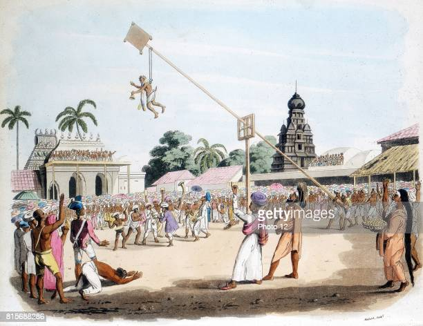 Man suspended by hooks swung through air at ceremony honouring Mariatale goddess of Smallpox at her temple at Negapattam Southern India Maritale was...