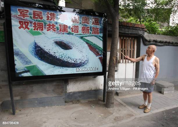 A man swats flies on trees near a poster advertising the Olympic Games near Hou Hai lake in Old Beijing China