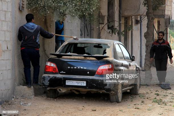 A man sweep his car after Assad regime's airstrikes hit residential areas of the deconflict zone in Ein Tarma town of Eastern Ghouta of Damascus...