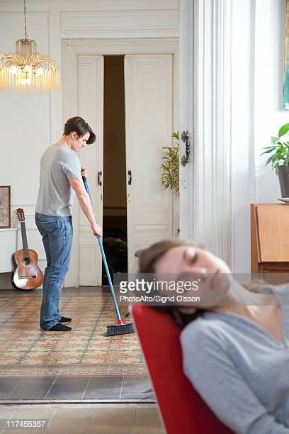 Man sweeping floor at home, woman napping in foreground