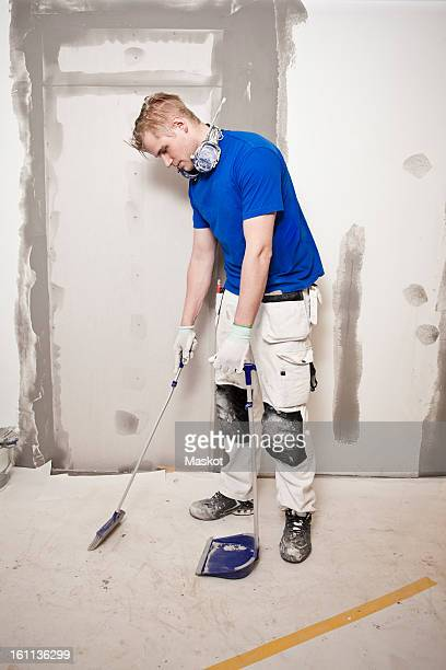 Man sweeping floor with dustpan and broom