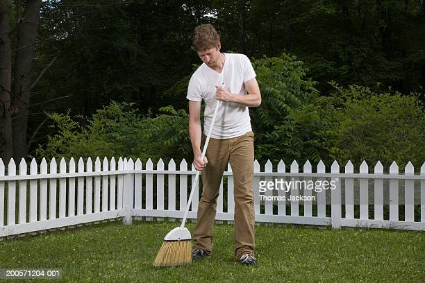 Man sweeping lawn with broom