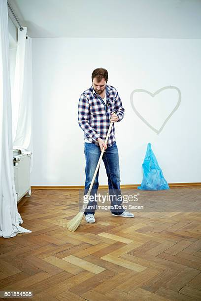 Man sweeping the parquet floor, heart shape on the wall, Munich, Bavaria, Germany