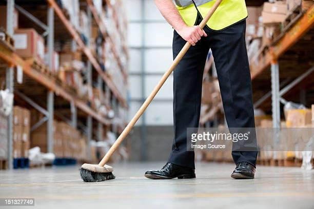 Man sweeping warehouse floor with broom