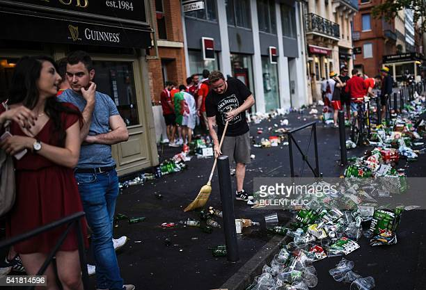 A man sweeps rubbish left on a street by Wales supporters before the Euro 2016 group B football match between Russia and Wales at the Stadium...