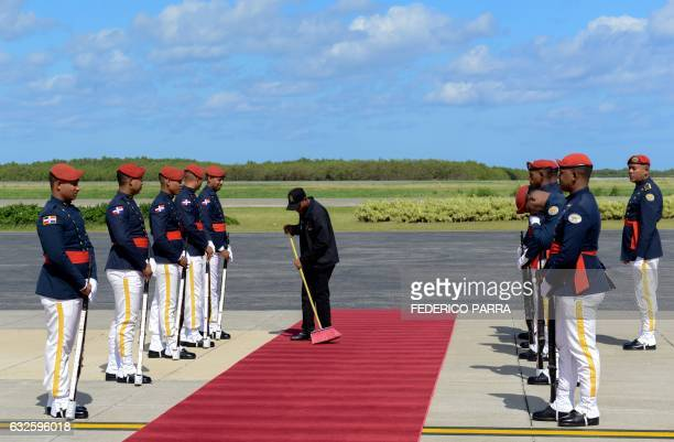 A man sweeps the carpet while members of the Navy stand guard at Punta Cana airport in the Dominican Republic on January 24 as they wait for the...