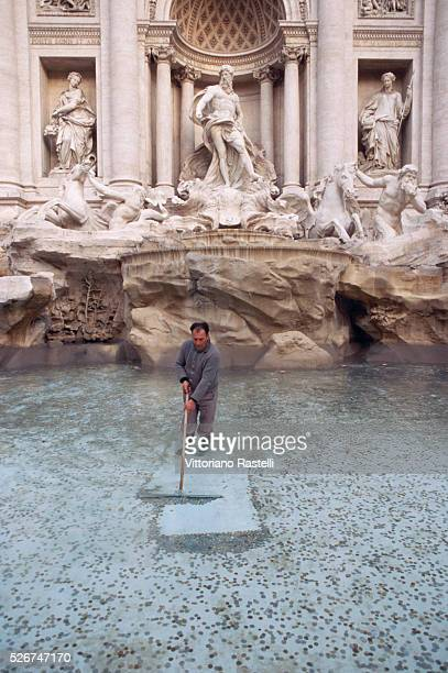 A man sweeps the coins from the Trevi Fountain in Rome